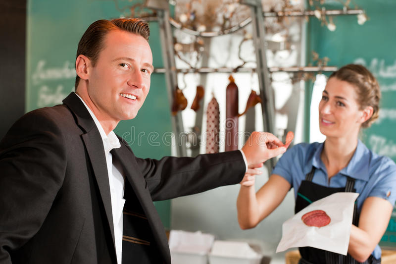Smiling Male Executive Holding Meat With Butcher stock photography