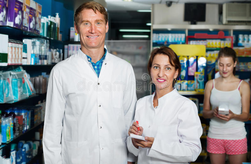 Smiling male and female pharmacists wearing white coats working royalty free stock image