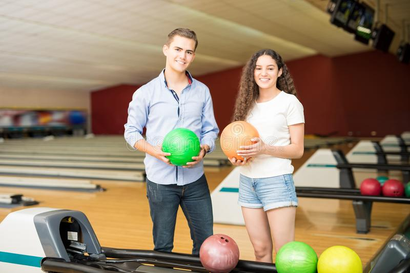 Teenage Friends Enjoying Sport Of Bowling In Club royalty free stock images