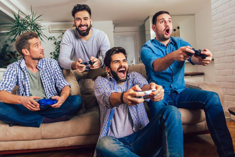 Male friends playing video games at home and having fun royalty free stock image
