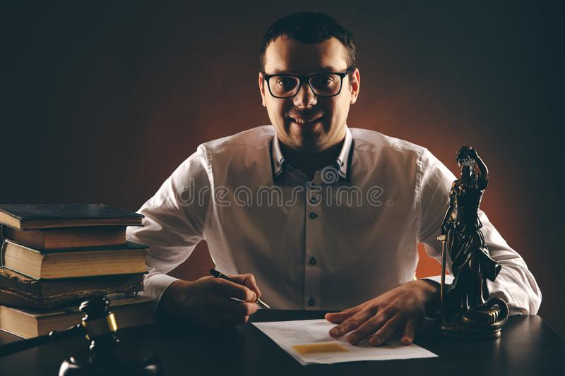Smiling male lawyer on his desk with paperwork. Libra and wooden gavel and books. royalty free stock photos