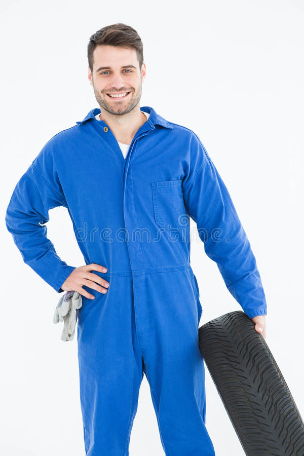 Smiling male mechanic holding tire. Portrait of smiling male mechanic holding tire on white background royalty free stock images