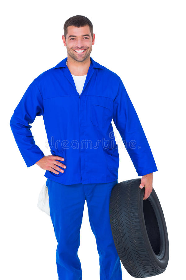 Smiling male mechanic holding tire. Portrait of smiling male mechanic holding tire on white background stock images