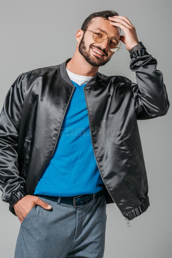 Smiling male model in stylish black bomber posing with hand in pocket. Isolated on grey background royalty free stock image