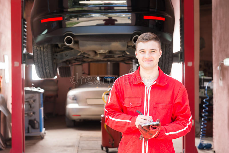 Smiling male motor mechanic standing making notes in front of a royalty free stock photo