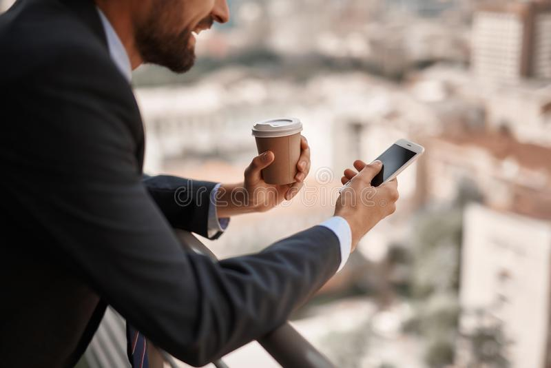 Smiling male in office suit reading massages on phone. Take a pause. Close up selective focus on smartphone in hand of businessman while he has coffee break on royalty free stock photos