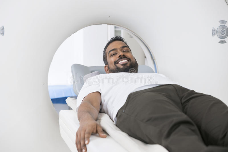 Smiling Male Patient Undergoing CT Scan In Examination Room royalty free stock image