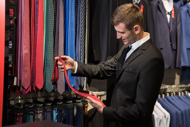 Man is picking up tie for suit in men`s shop. royalty free stock image