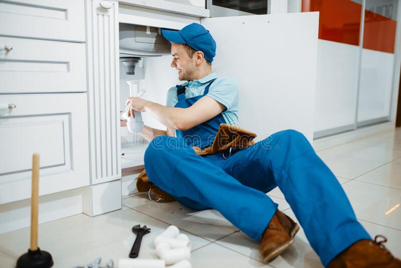 Smiling male plumber in uniform holds drain pipe stock images