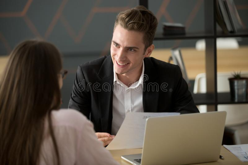 Smiling male recruiter discussing cv with female job applicant royalty free stock photo