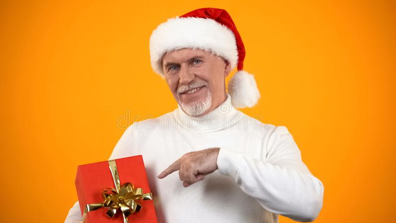 Smiling male retiree in santa claus hat pointing finger at red giftbox, discount stock photo