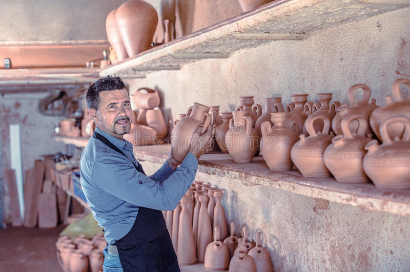 Smiling male sculptor in pottery atelier. Smiling male sculptor having ceramics in hands and standing in pottery atelier royalty free stock photos