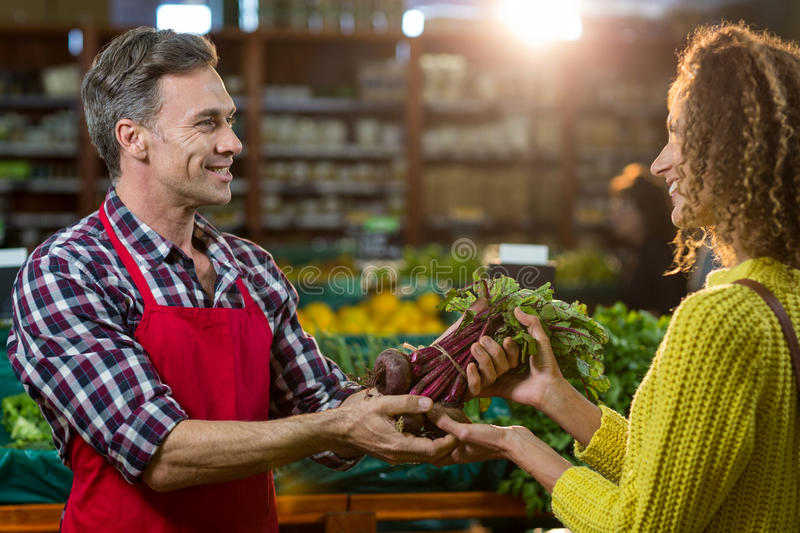 Smiling male staff assisting a woman with grocery shopping stock photo