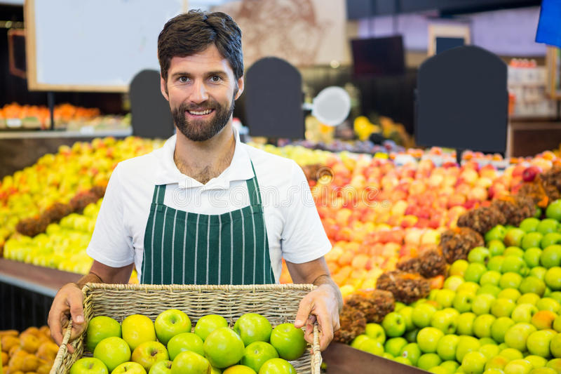 Smiling male staff holding a basket of green apple at supermarket stock photography