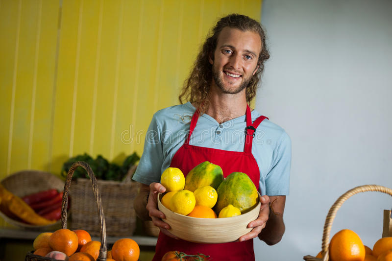 Smiling male staff holding fruits in basket at organic section stock images
