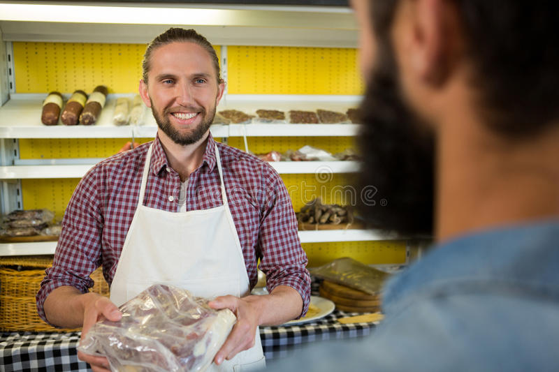 Smiling male staff holding a meat packet at counter royalty free stock photo