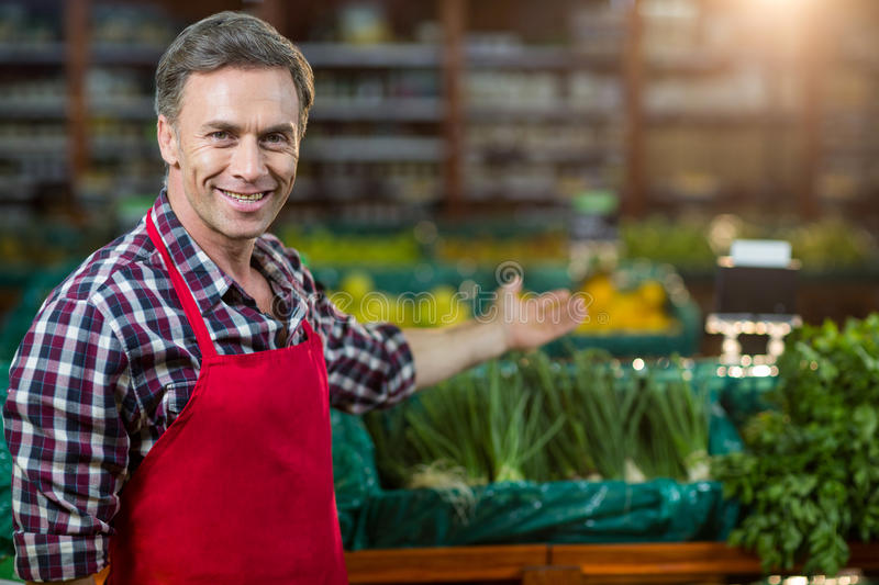 Smiling male staff showing organic section royalty free stock photos