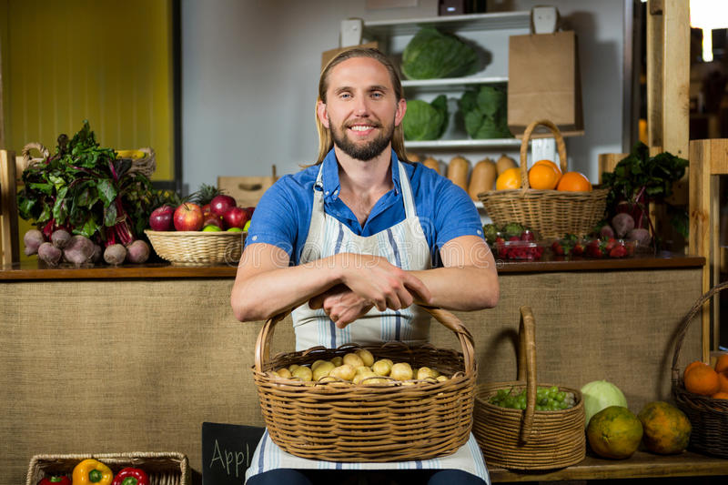 Smiling male staff siting with basket of potatoes at organic section stock photos