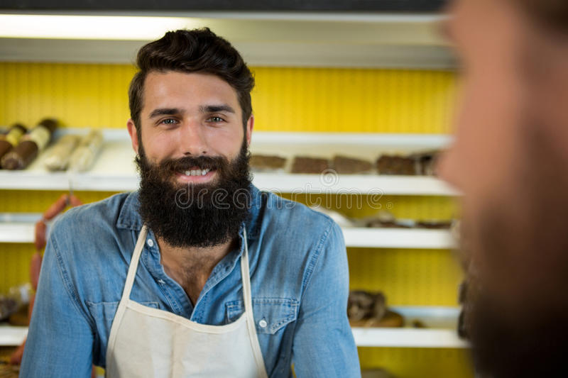Smiling male staff standing at meat shop stock photo