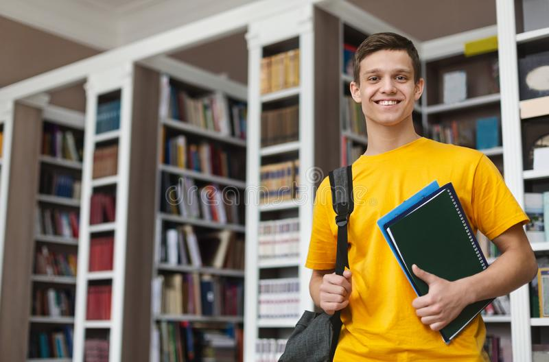 Smiling guy posing in library, holding books and notes stock images