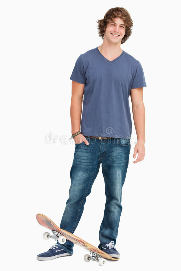 Smiling male student with a skateboard. Against a white background stock photography