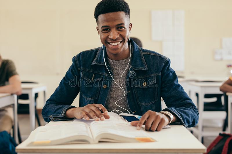 Smiling male student in university classroom. Smiling male student in college classroom with books. Teenage boy sitting in college classroom stock image