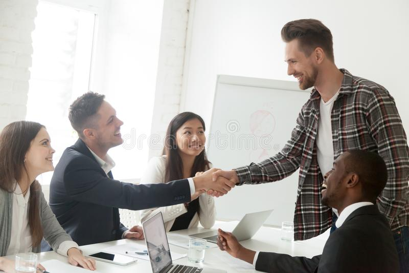 Team leader handshaking new member to diverse work group stock photos