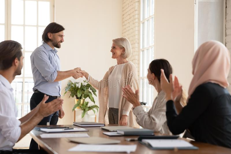 Smiling male team leader shaking hands with mature colleague. royalty free stock images