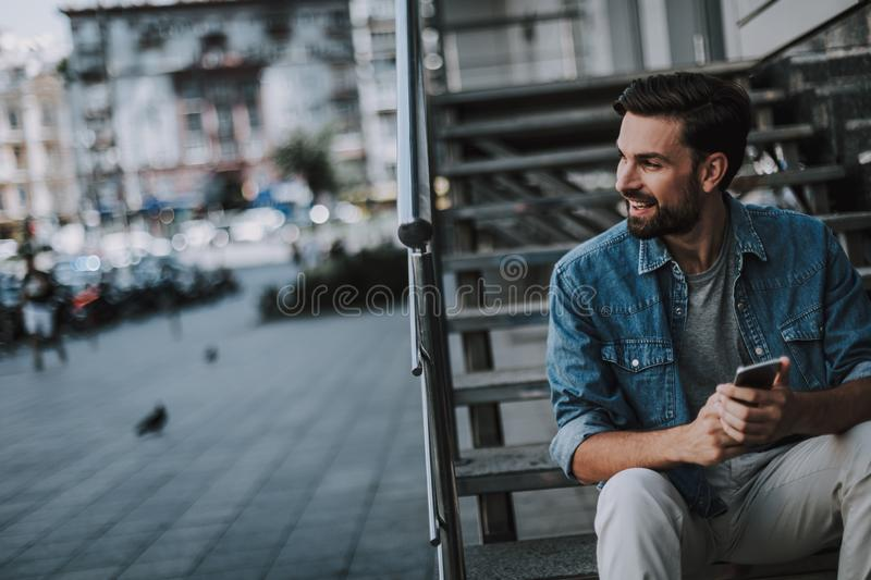 Smiling male using the modern phone outdoor royalty free stock photos