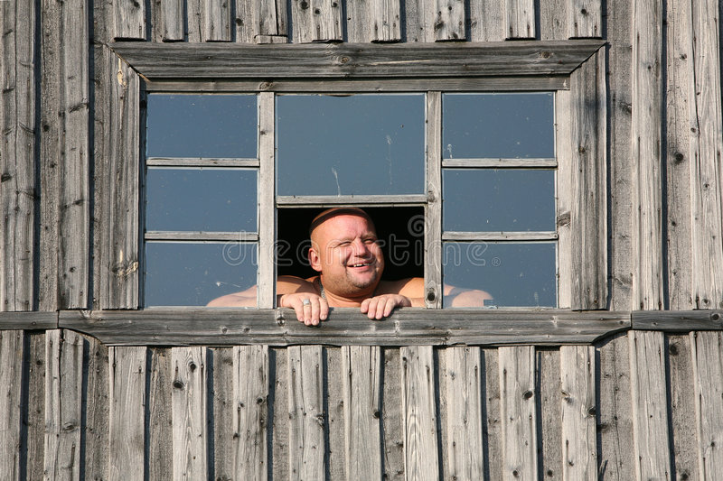 The smiling man. In a garret window stock photography