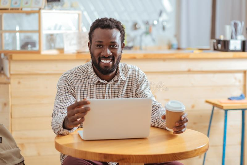 Smiling man adjusting angle of laptop screen. Necessary adjustment. Charming young man sitting at the table, holding a cup of coffee and changing the angle of stock photos
