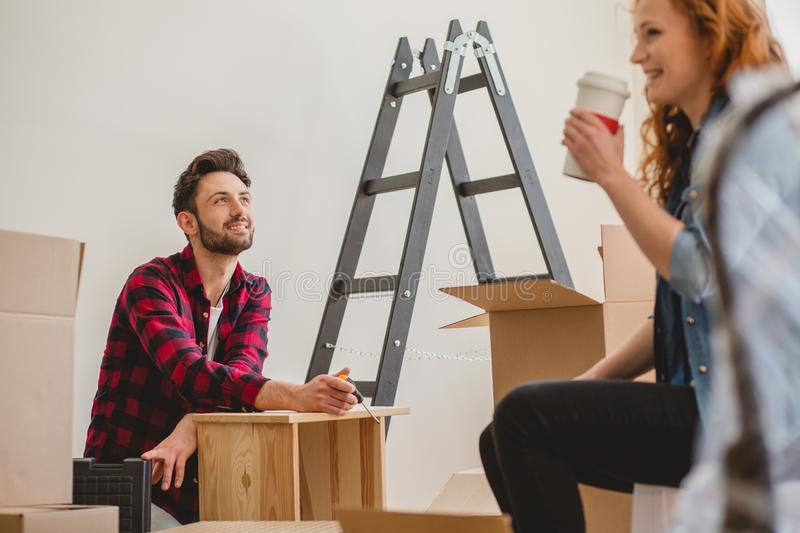 Smiling man assembling a cabinet and his girlfriend drinking coffee while furnishing interior. Smiling men assembling a cabinet and his girlfriend drinking stock images