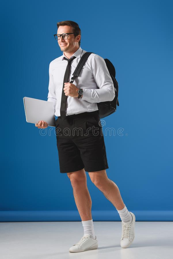 Smiling man with backpack holding laptop and looking away. On blue royalty free stock images
