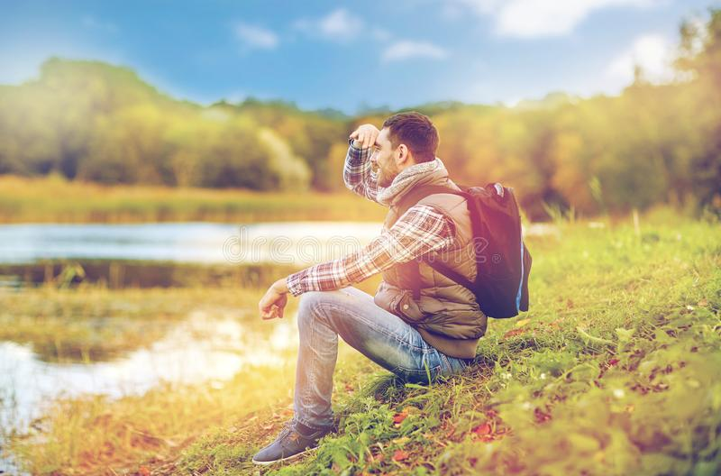 Smiling man with backpack resting on river bank. Adventure, travel, tourism, hike and people concept - smiling man with backpack resting on river bank stock images