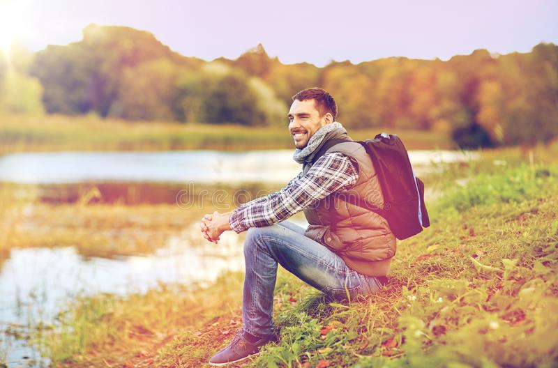 Smiling man with backpack resting on river bank. Adventure, travel, tourism, hike and people concept - smiling man with backpack resting on river bank stock photo