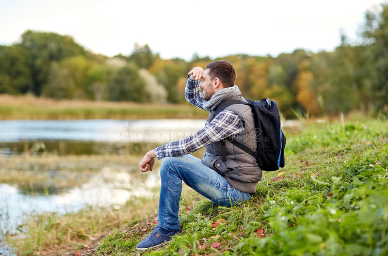 Smiling man with backpack resting on river bank. Adventure, travel, tourism, hike and people concept - smiling man with backpack resting on river bank royalty free stock photos