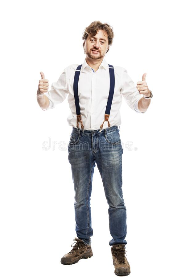 A smiling man with a beard in jeans and a white shirt stands and holds thumbs up. Full height. Isolated on a white background. stock photos