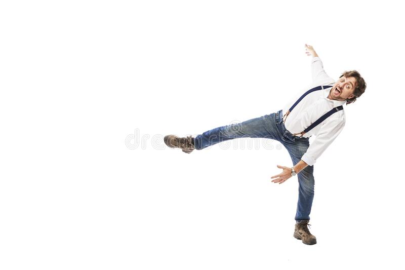 Smiling man with a beard in a white shirt and jeans is falling. Full height. Isolated on a white background. Space for text stock images