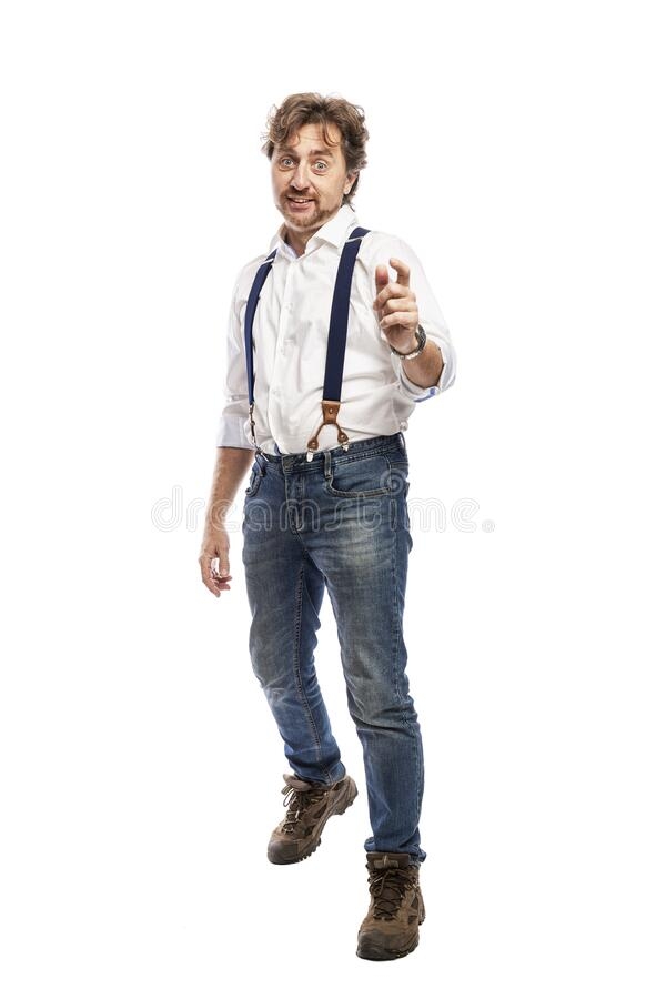 A smiling man with a beard in a white shirt and jeans points forward with his index finger. Full height. Isolated on a white stock photos
