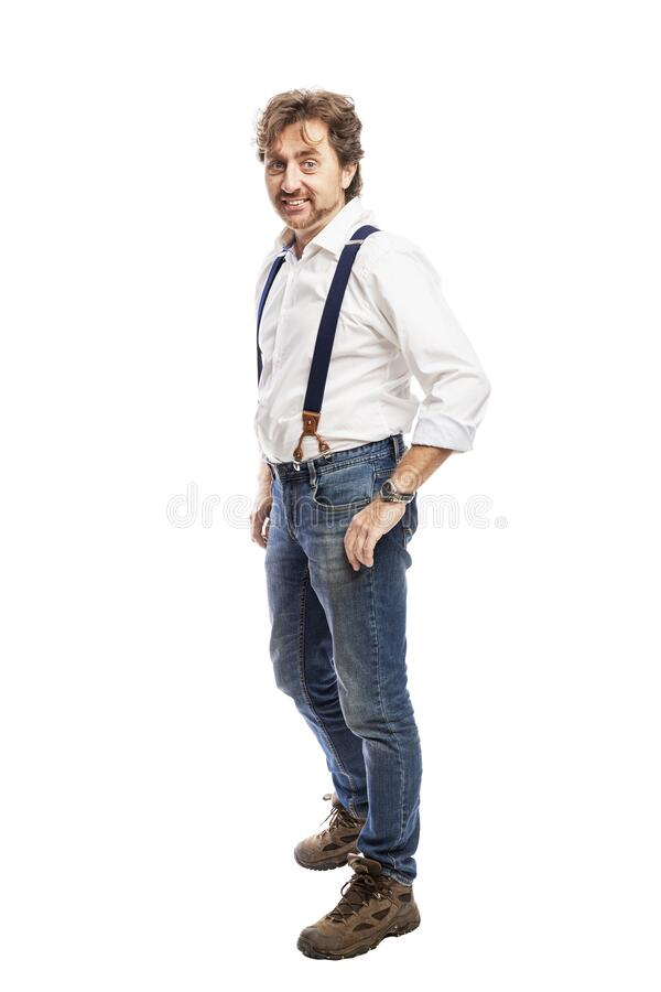 A smiling man with a beard in a white shirt and jeans stands holding his hands in his pockets. Full height. Isolated on a white royalty free stock image