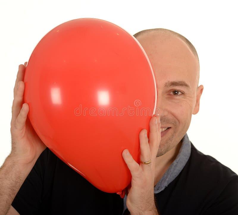Smiling man behind red balloon stock photo