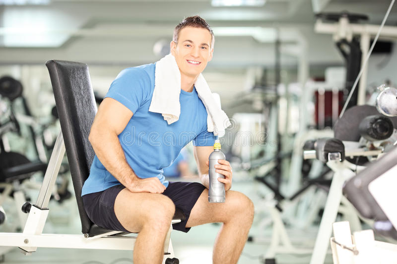 Smiling man on a bench drinking water after exercise in fitness. Smiling man seated on a bench drinking water after exercise in fitness gym, with very shallow stock photos