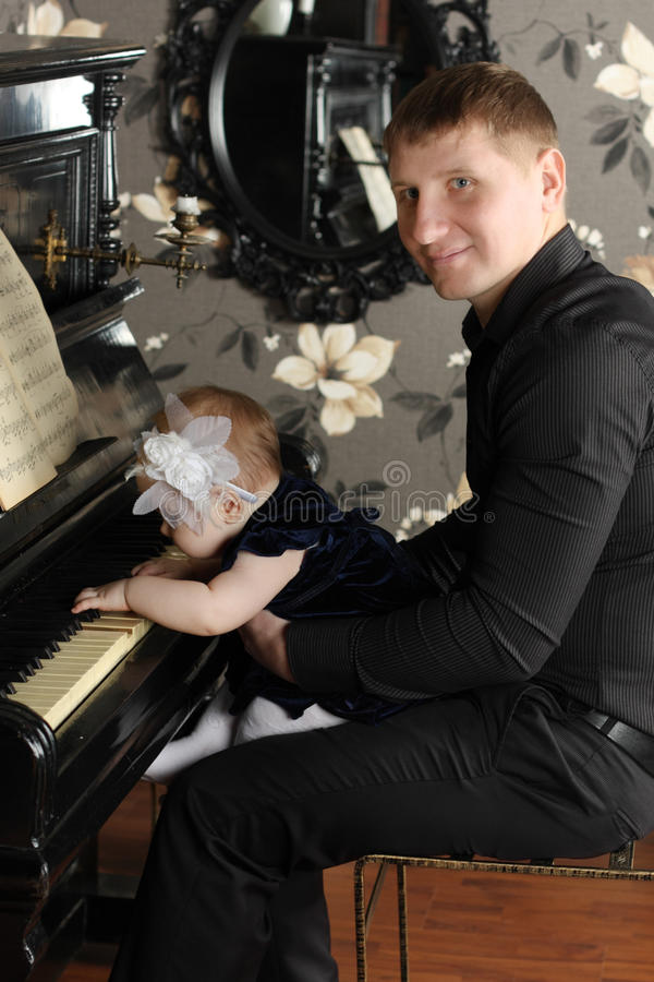 Smiling man in black with cute baby sits at piano royalty free stock image