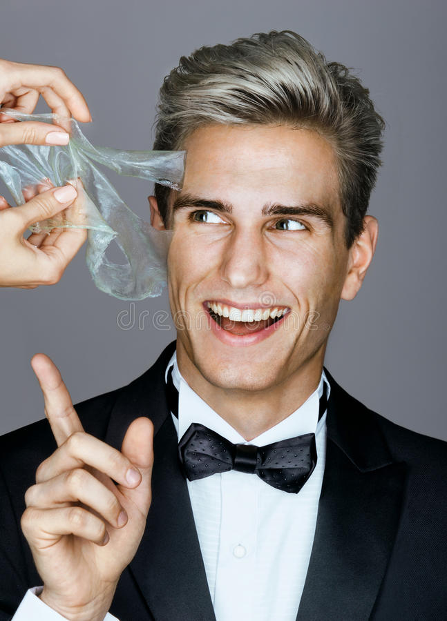Smiling man in black suit removes peeling off a facial mask. royalty free stock photography