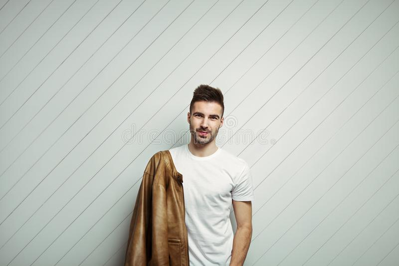 Smiling man in blank t-shirt wearing leather jacket on the shoulder, white wooden background. Studio indoors stock photography