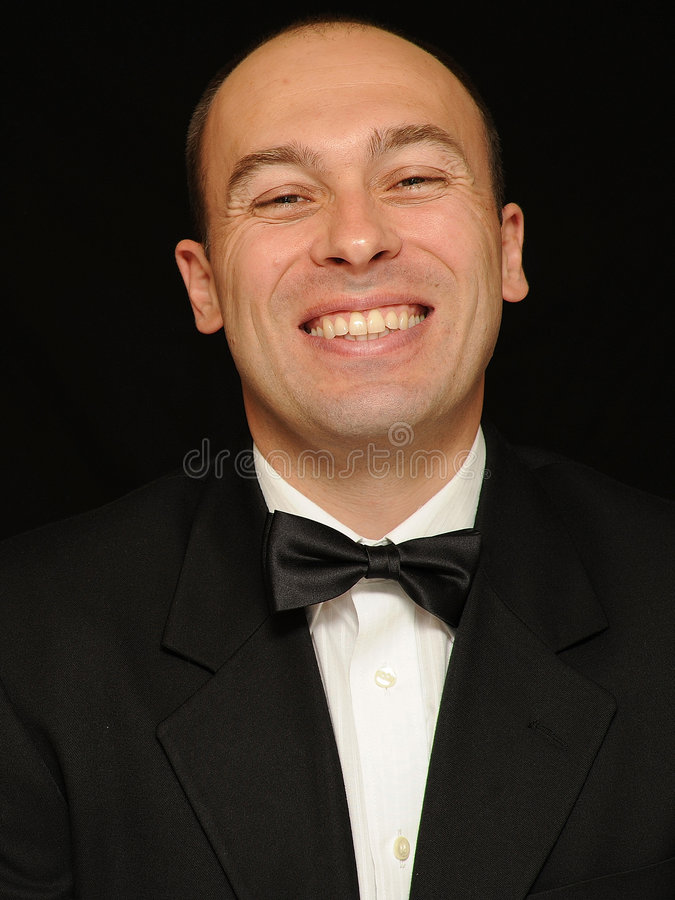 Smiling man in bow tie. Head shot of a smiling man in dark jacket and bow tie isolated on black background, caucasian/white royalty free stock images