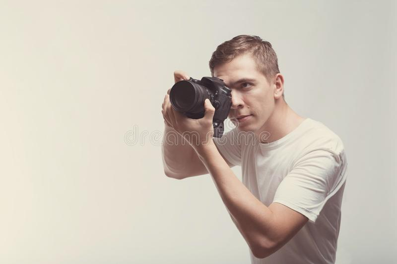 Smiling Man with camera isolated on light background. Young man holding digital camera and making photo looking on side. Lifestyle stock photos
