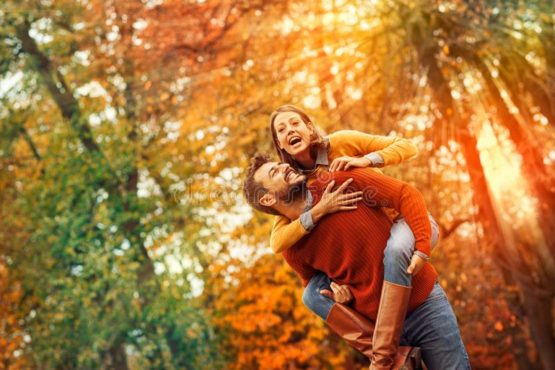 Smiling man carrying woman piggyback outdoor royalty free stock images