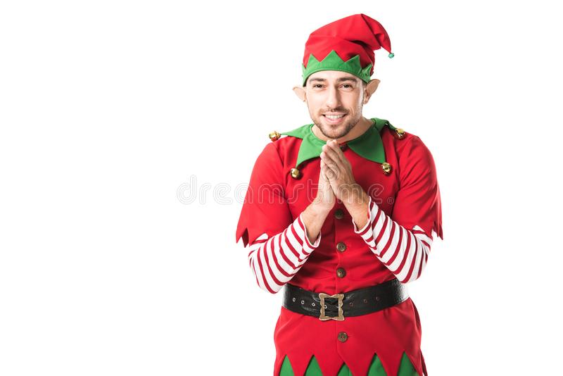 smiling man in christmas elf costume looking at camera and rubbing hands in anticipation isolated stock image
