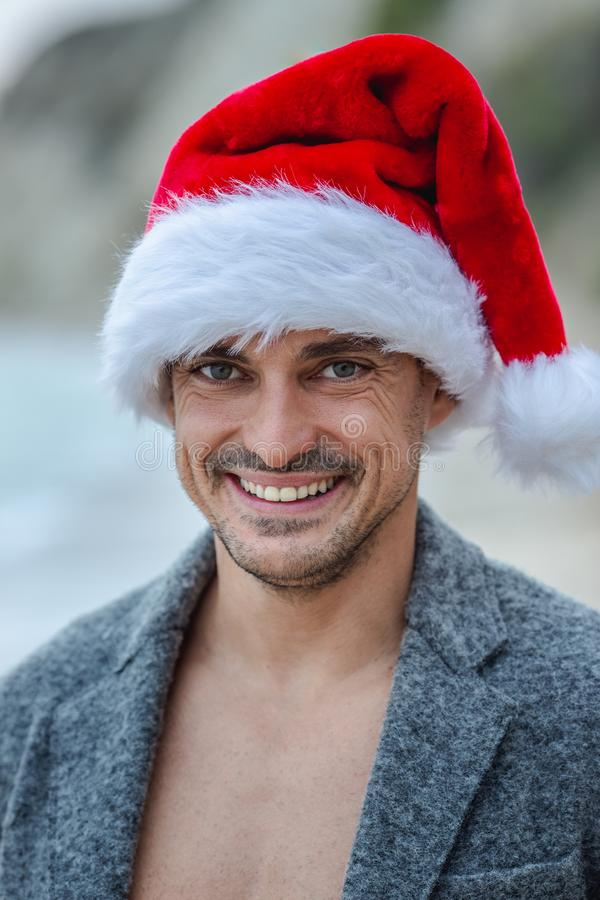 Smiling man with Christmas hat. Smiling sexy man with christmas hat on the beach royalty free stock image